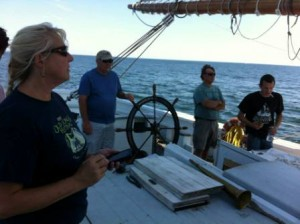 Shipskeeper, Bill, takes a turn at the wheel while director, Joanne, looks on